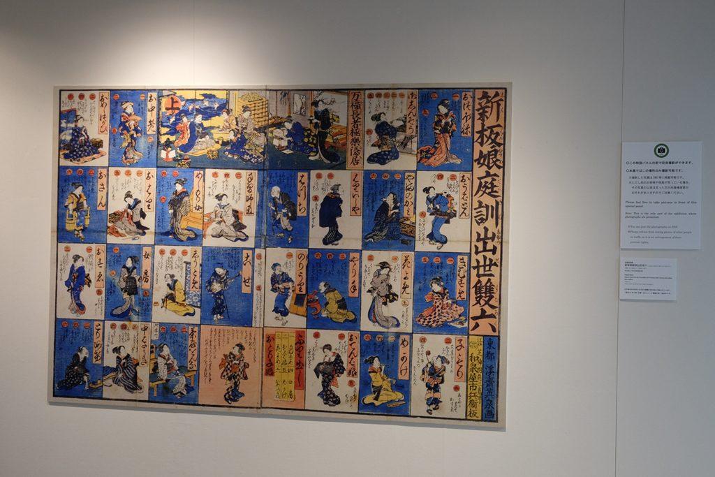 撮影可能エリアに掲げられた江戸時代の女性版人生ゲーム。子供や孫に囲まれてお金に不自由しない老後が幸福な人生のゴール?